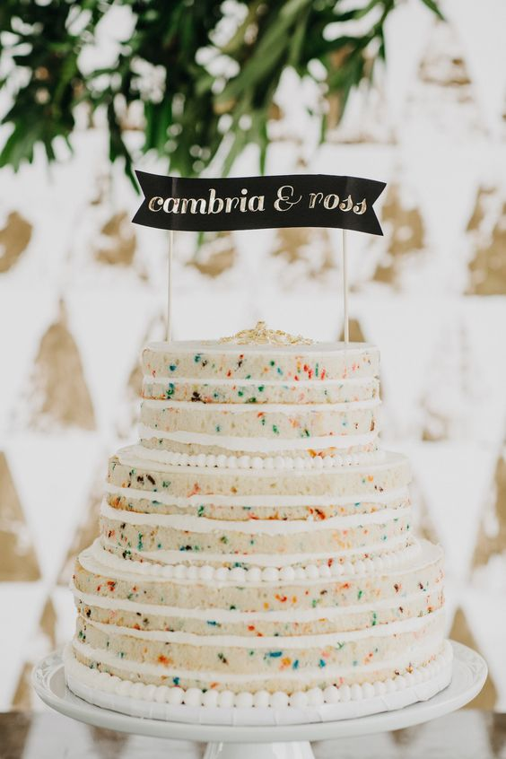 a colorful sprinkle naked wedding cake with gold leaf on top and a black and gold topper for a fun wedding