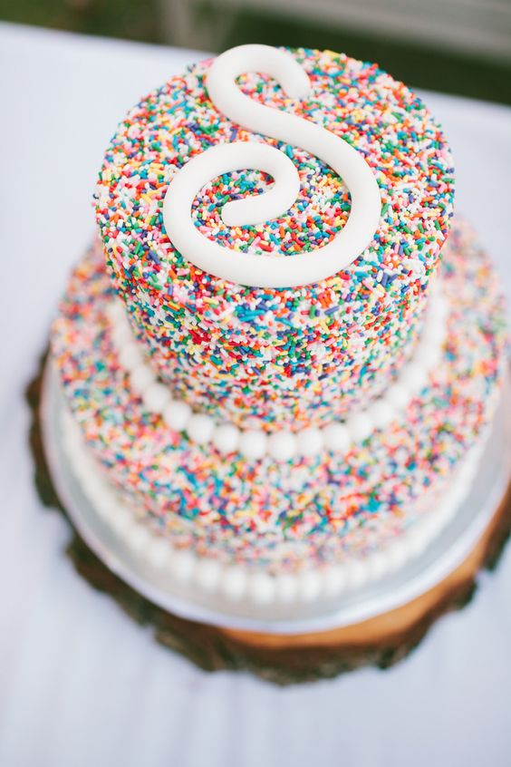 a colorful sprinkle wedding cake with a white S monogram on top for a party-themed wedding