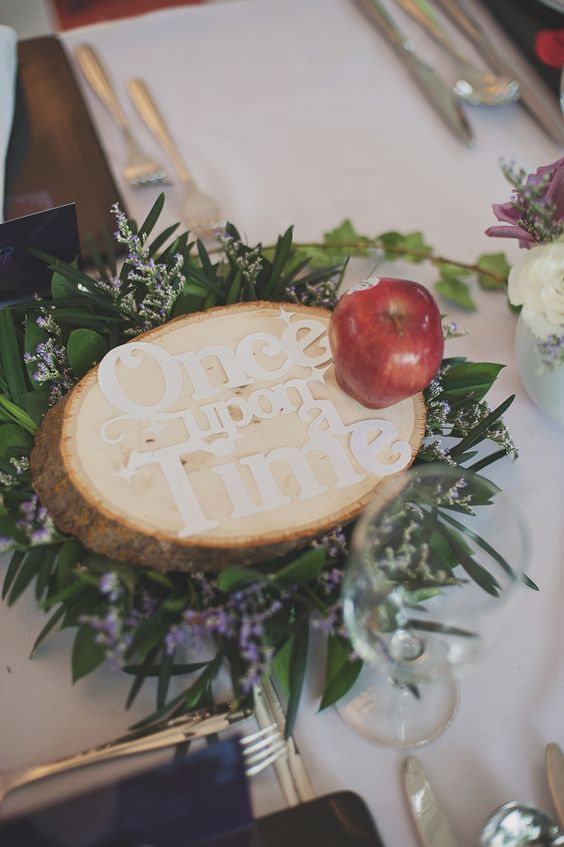 a cool Disney-themed wedding centerpiece with fresh blooms and greenery, a wooden slice with letters and a single apple
