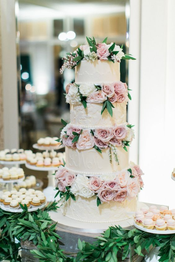 a cute wedding cake with white patterned tiers, lilac and white blooms between the tiers is veyr softening