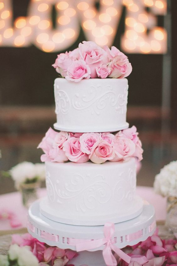 a cute white patterned wedding cake with pink roses between the tiers looks super cool