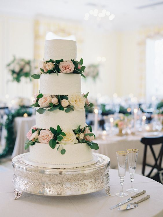 a cute white textural wedding cake with blush and neutral blooms and greenery is timeless