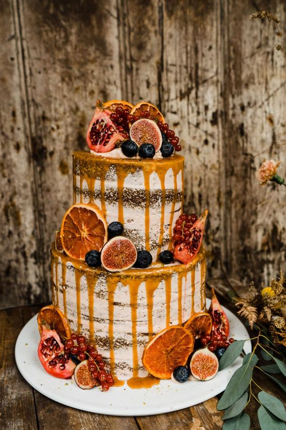 a decadent fall semi naked wedding cake decotated with fresh berries, figs, pomegranates, candied citrus and caramel drip