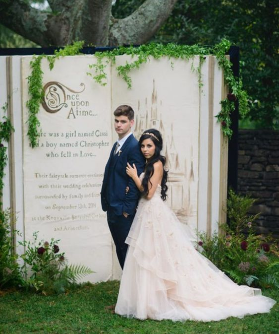 a fairytale book wedding backdrop with greenery is a very creative Disney wedding idea