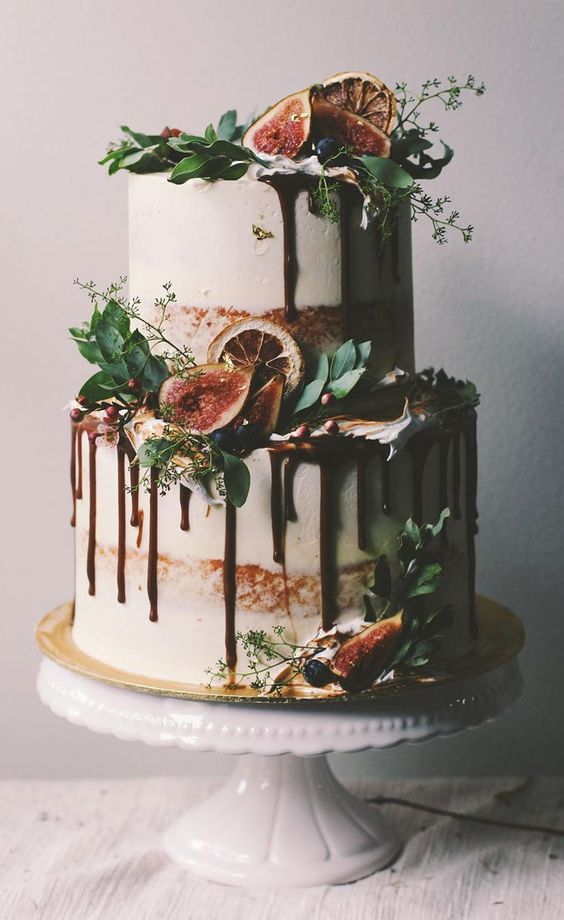 a fall semi naked wedding cake with greenery, berries, figs, dried citrus and chocolate drip