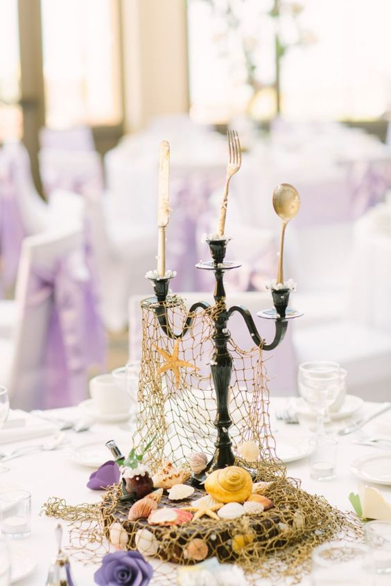 a fun Disney wedding centerpiece with a candelabra with cutlery, a fish net and shells and star fish
