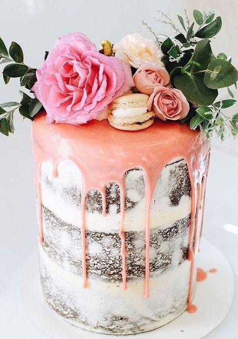 a glam semi naked wedding cake with pink drip, pink flowers and macarons plus greenery for a spring or summer wedding