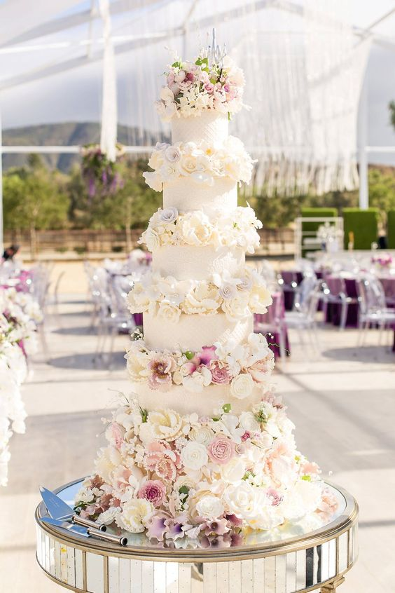 a glam wedding cake with white patterned tiers, white and blush blooms, very lush and chic