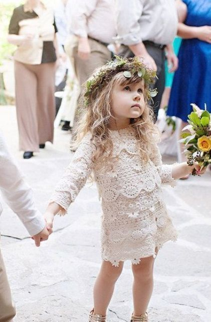 a gorgeous boho lace flower girl dress with long sleeves, an over the knee skirt and a high neckline