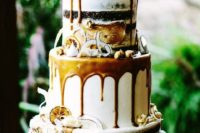 a gorgeous fall boho wedding cake with caramel drip, candied lemon and shaved coconut plus an elegant topper