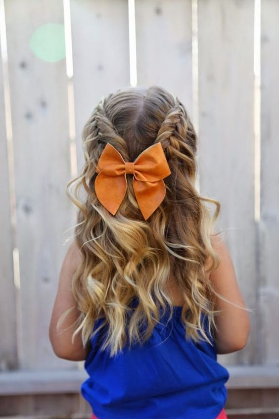 a half updo with braids on top and waves down, a bold orange bow for an accent is a very lovely and girlish idea