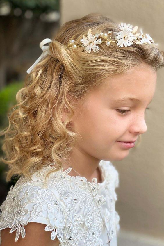 a half updo with curls and a white silk flower and bead crown is a stylish, chic and formal idea for a refined flower girl look