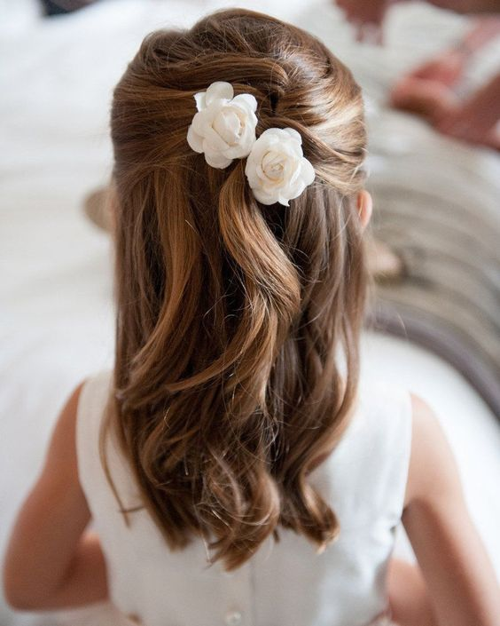 a half updo with twists and waves down, with white silk blooms will match a classic and formal flower girl look