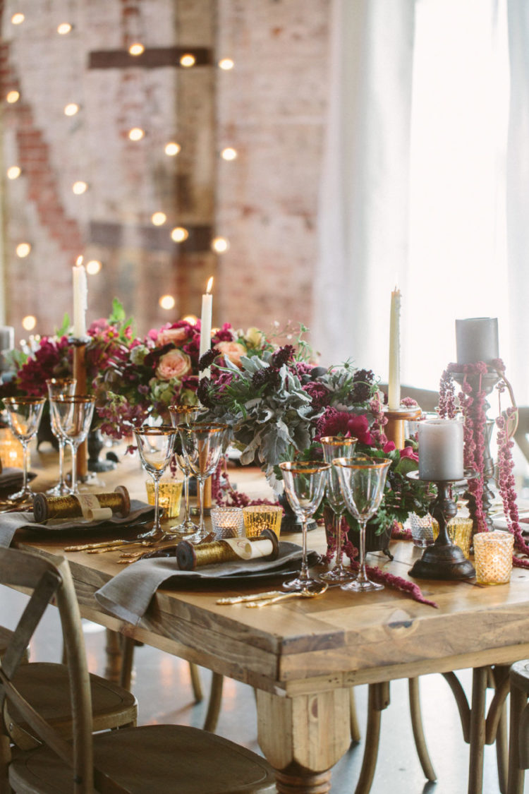 a lush and moody Sleeping Beauty wedding tablescape with moody florals, pale greenery, candles, gold rimmed glasses