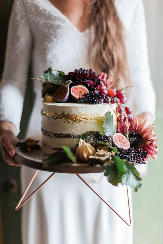 a lush fall wedding cake topped with grapes, figs, dark blooms, leaves and other stuff and gold leaf