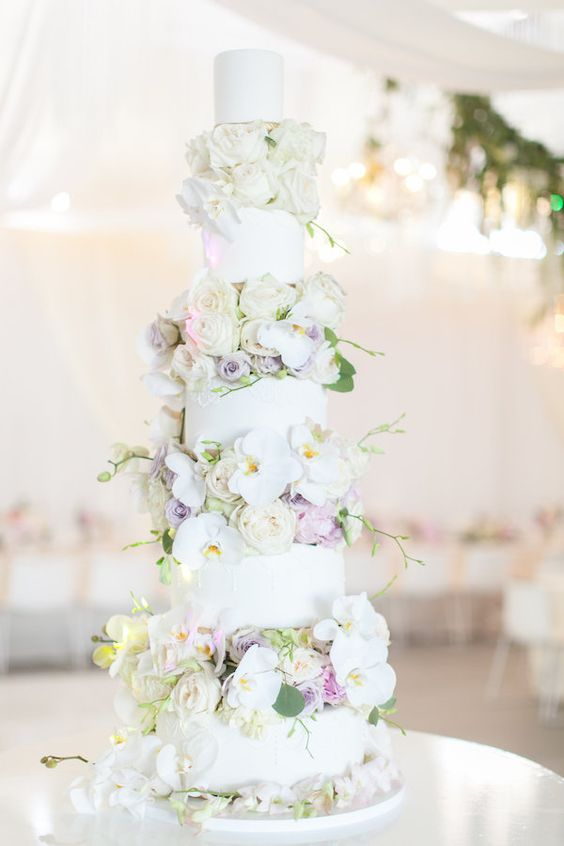 a luxurious white wedding cake with white orchids, lilac and blush blooms between the tiers
