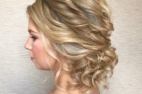 a messy twisted low updo with curls and bangs is a very romantic option, which fits many bridal styles