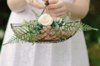 a mini wire basket with greenery and a bloom is a chic idea with a rustic feel