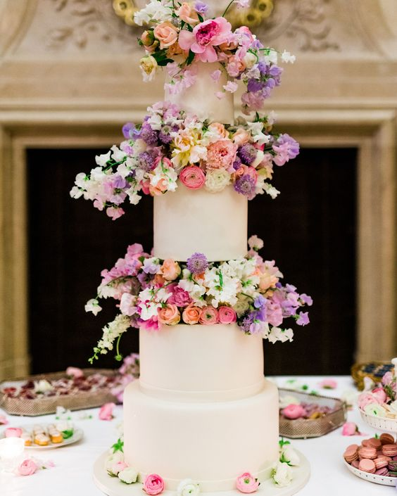 a modern white wedding cake with super bright and blush blooms between the tiers looks wow