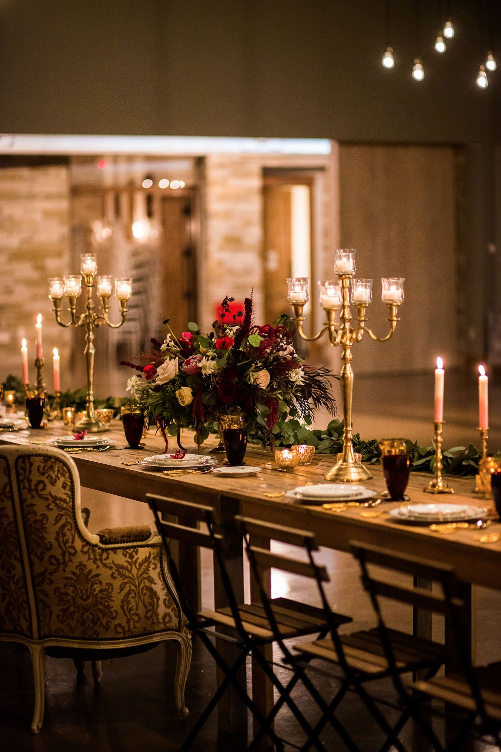 a moody Beauty and the Beast wedding tablescape with candlelabras, gold and burgundy glasses, a lush floral centerpiece and a greenery runner