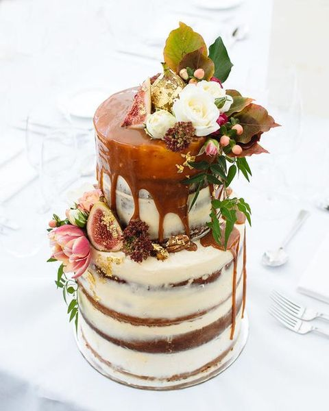 a naked fall wedding cake topped with flowers and leaves, with figs and gold leaf plus caramel drip