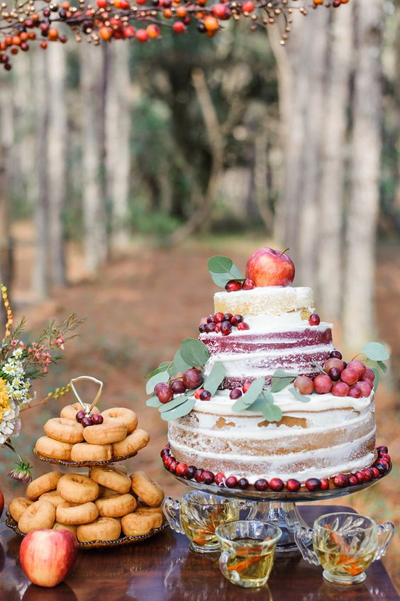 a naked fall wedding cake with apples, grapes and cranberries plus leaves for a fall wedding with a rustic touch