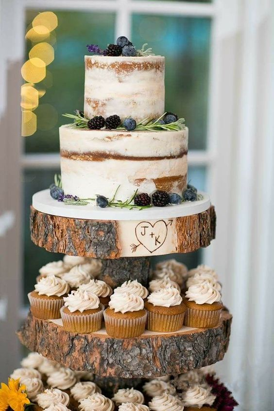 a naked fall wedding cake with blackberries and blueberries, with greenery and some blooms served on a wood slice stand