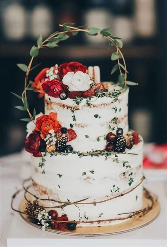 a naked wedding cake decorated with bold blooms, greenery, gilded berries and twigs for a summer wedding