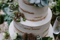 a naked wedding cake decorated with succulents, greenery, white blooms and berries is a cool and chic idea