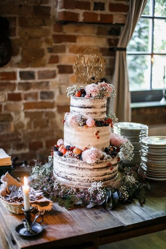 a naked wedding cake topped with berries and fruits, with pink blooms and macarons and an elegant topper
