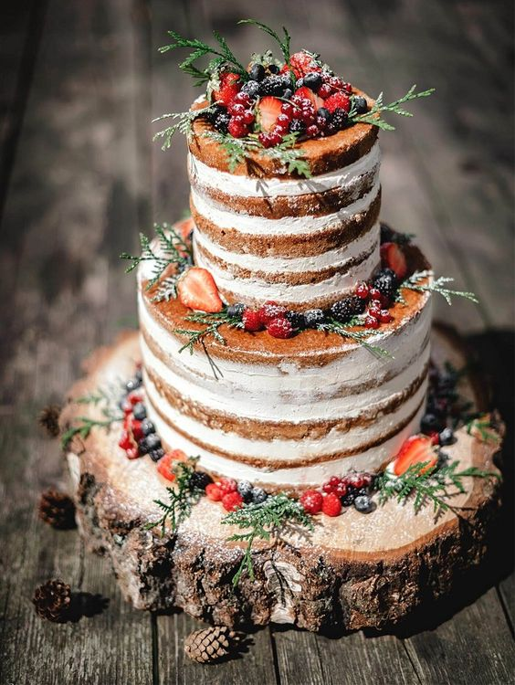 a naked wedding cake topped with sugared berries, greenery served on a wood slice for a rustic wedding