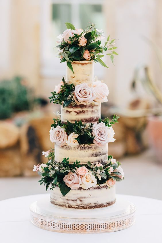 a naked wedding cake with blush and lilac blooms and greenery between the tiers is just wow