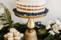 a naked wedding cake with citrus and blueberries for a cool summer wedding or a destination one