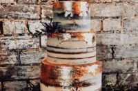 a naked wedding cake with gold leaf, berries, thstles, dried branches and a calligraphy topper