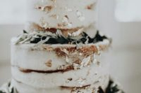 a naked wedding cake with greenery and gold leaf is a chic idea for a neutral wedding with a rustic feel