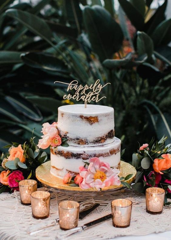 a naked wedding cake with pink and peachy blooms and a calligraphy topper for a summer or tropical wedding