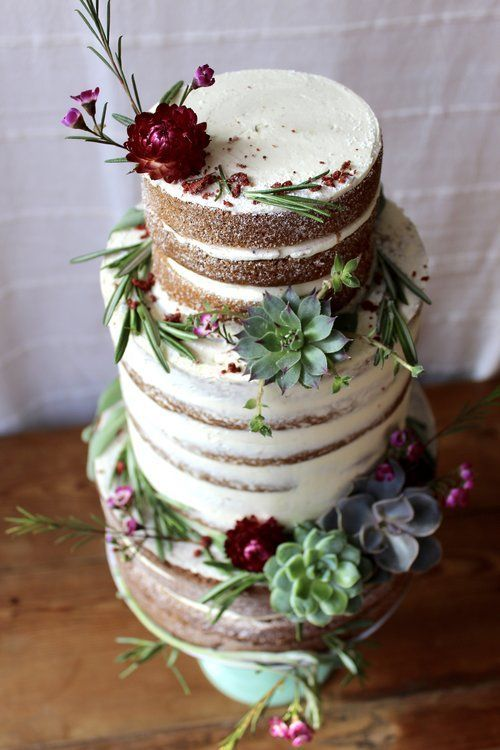 a naked wedding cake with succulents of various shades and burgundy blooms, with herbs for a bold look