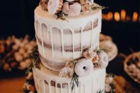a naked wedding cake with white chocolate drip, greenery, glazed donuts and thistles for a winter wedding