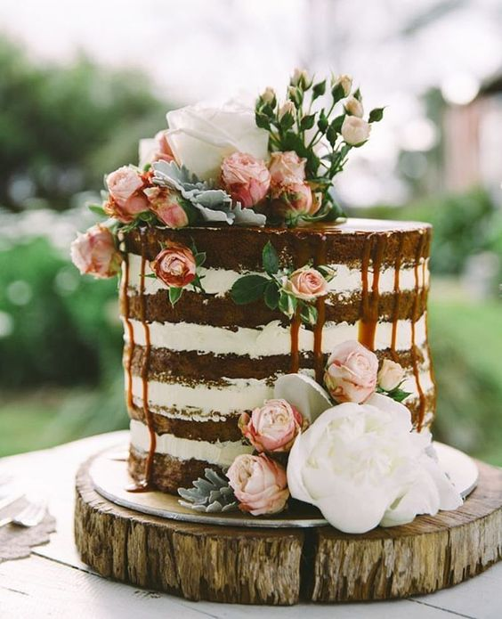 a naked wedidng cake with caramel drip, with pink and white blooms is amazing for summer or for spring