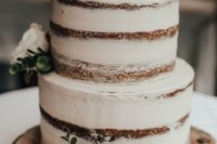 a neutral naked wedding cake with succulents, greenery and light pink blooms for a rustic wedding