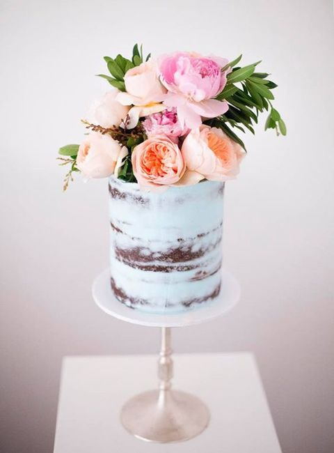 a pale blue naked wedding cake with n oversized fresh floral topper looks wow