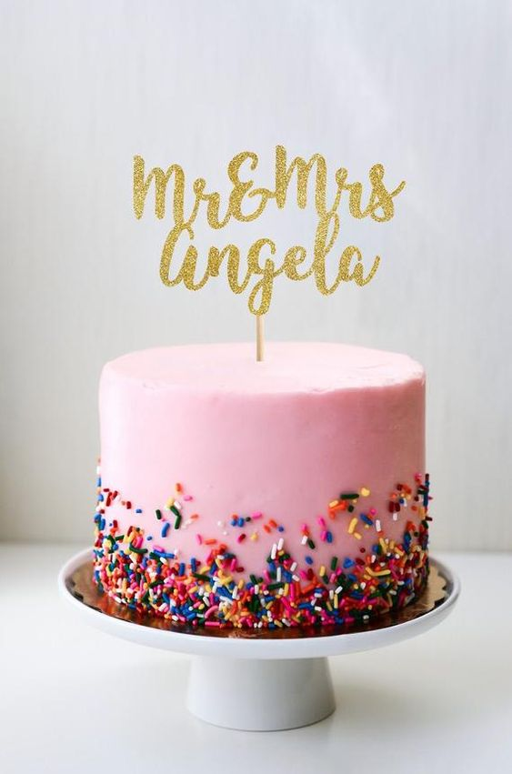 a pink wedding cake with colorful sprinkles and a gold calligraphy topper for a fun and colorful wedding