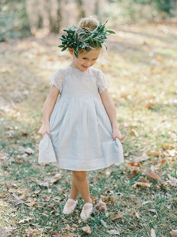 a powder blue A-line knee dress with an illusion neckline and sleeves, white sandals and a greenery crown