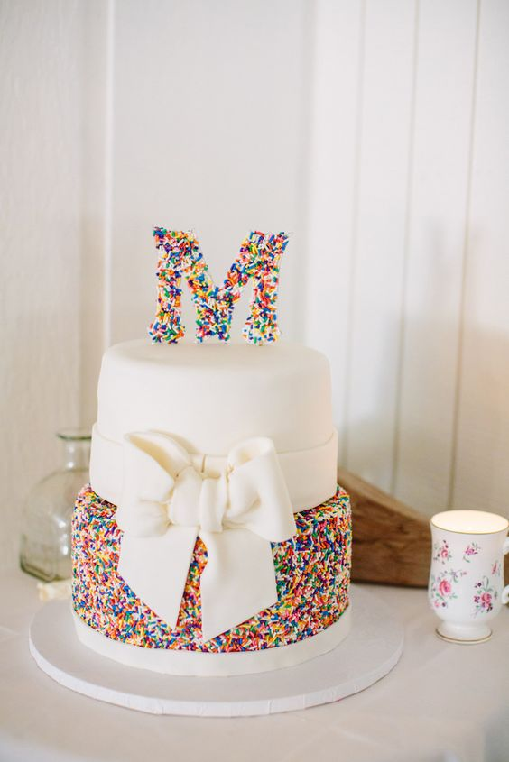 a pretty wedding cake with a white and colorful sprinkle tier, a sugar bow and a sprinkle monogram for fun