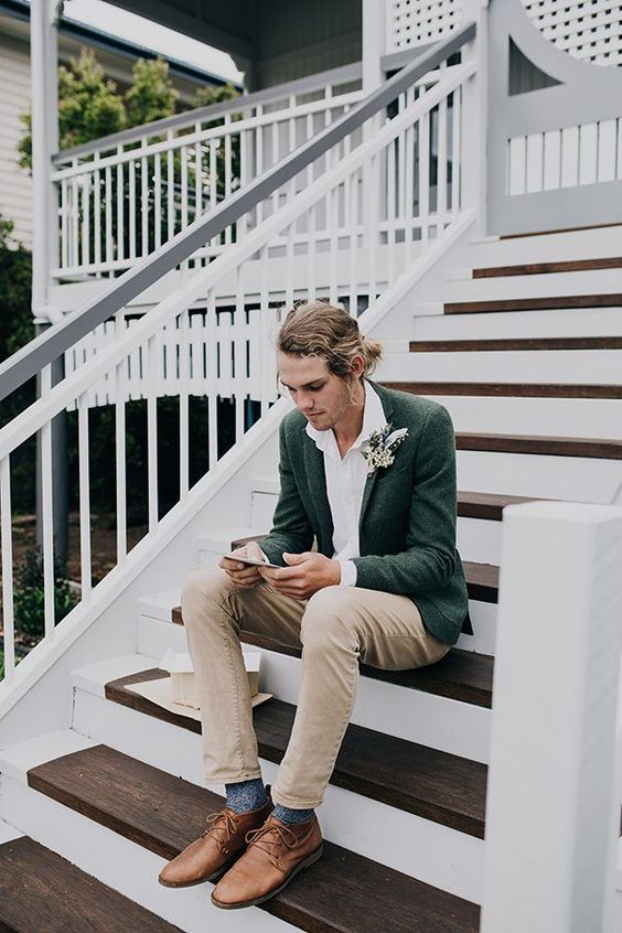 a relaxed look with a boho feel is done with a dark green jacket, a white shirt, tan pants, brown shoes and blue socks