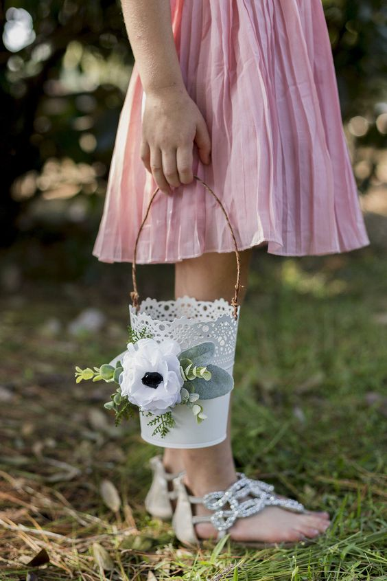 a romantic flower girl basket is designed with soft white anemone flowers and artificial greenery