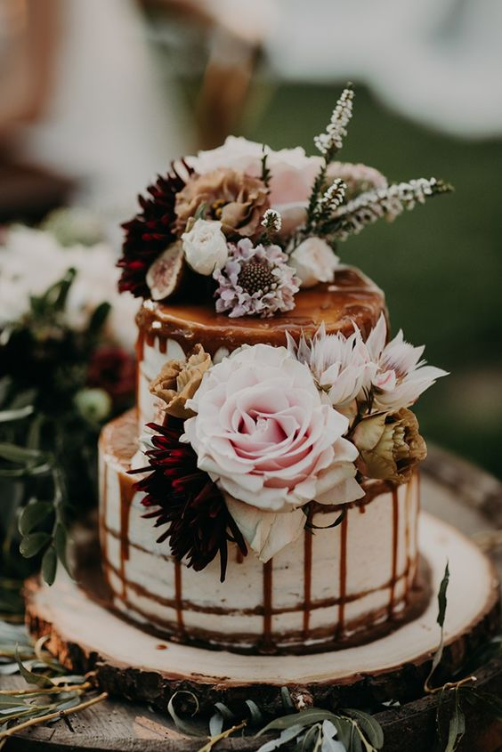 a romantic naked wedding cake with blush and burgundy blooms, with greenery and white blooms and caramel drip