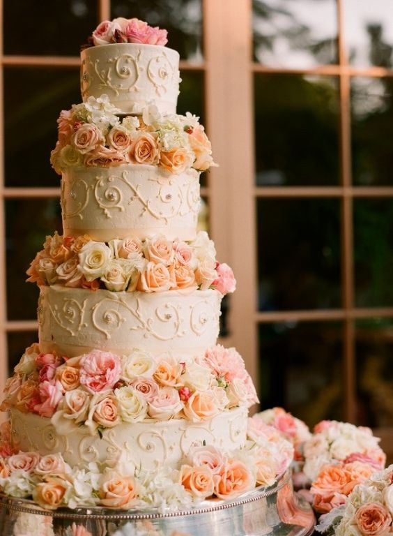 a romantic wedding cake with patterned tiers and peachy and pink blooms between the tiers
