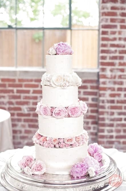 a romantic white wedding cake with blush and white blooms between the tiers
