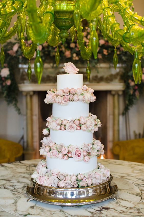 a romantic white wedding cake with blush blooms and a blush rose on top is very beautiful